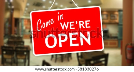 We are open sign hanging on a glass storefront #581830276