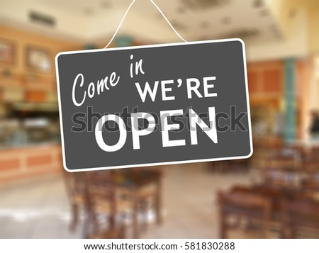 We are open sign hanging on a glass storefront #581830288
