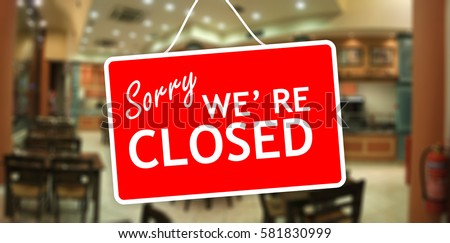 Closed for holiday. Sorry we are closed red tag hanging on a glass storefront #581830999