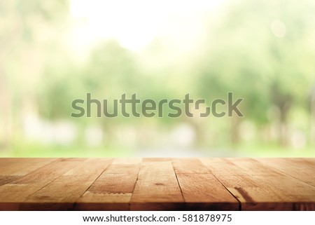 Wood table top on blur green background of trees in the park - can be used for display or montage your products #581878975