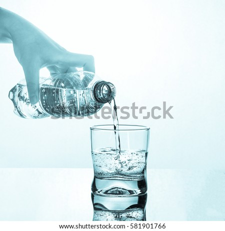 water pouring from the plastic water into the glass, healthy living concept #581901766