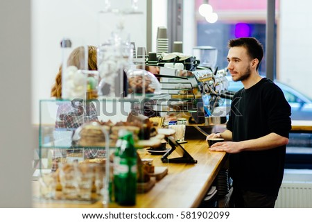 Smiling friendly barista speaking with  customer and drinking coffee in coffee shop. Coffee culture concepts with real people models. 