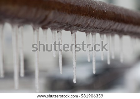 Icicles hanging from a brown pipe. Frozen water and metal surface, winter time concept. selective focus shallow depth of field photo Royalty-Free Stock Photo #581906359