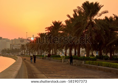 DOHA, QATAR - NOVEMBER 2, 2016. Al Corniche waterfront in Doha at sunrise, with palms, people and buildings in the distance. #581907373