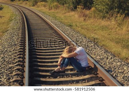 Depressive woman sitting on a railway track Royalty-Free Stock Photo #581912506