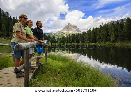 Happy family with teenager taking brake during trekking day on Dolomites mountain in summer time in Italy. Concept of travel, friendly family. #581931184
