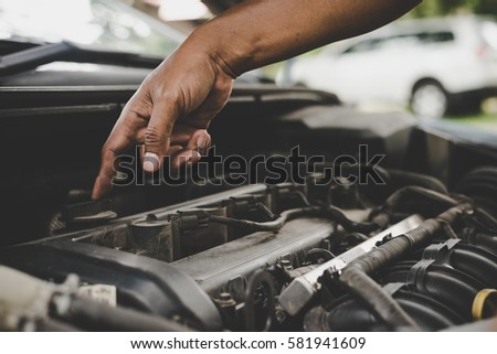Man with checking car engine. #581941609