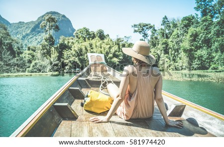 Young woman traveler on longtail boat trip at island hopping in Cheow Lan Lake - Wanderlust and travel concept with adventure girl tourist wanderer on excursion in Thailand - Retro turquoise filter #581974420