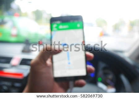 Picture blurred  for background abstract and can be illustration to article of Hand using a smartphone while driving a car #582069730