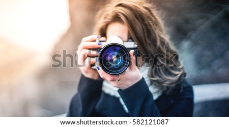 Young woman girl photographer with blue camera lens