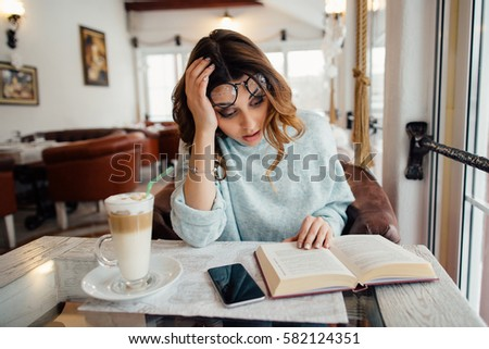 Tired student girl reading scientific literature in cafe  #582124351