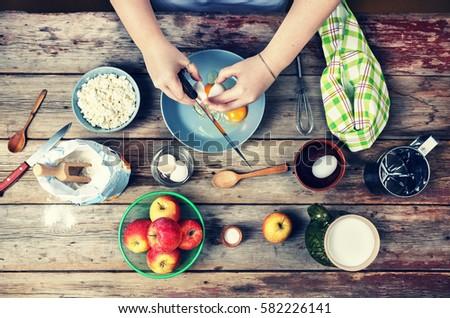 Cooking food. Woman cook breaks egg dough. #582226141