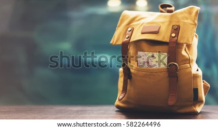 Hipster yellow backpack and map closeup. View from front tourist traveler bag on background blue sea aquarium. Person hiker visiting ocean museum in Barcelona on backdrop, blank blurred mock up Royalty-Free Stock Photo #582264496