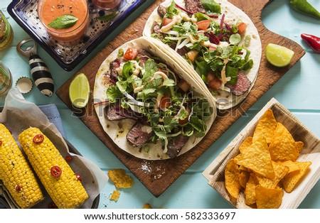 Mexican picnic party outdoor - quesadillas, corn, nachos, gazpacho and beer #582333697