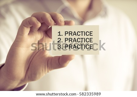 Closeup on businessman holding a card with text PRACTICE, PRACTICE, PRACTICE, business concept image with soft focus background and vintage tone Royalty-Free Stock Photo #582335989