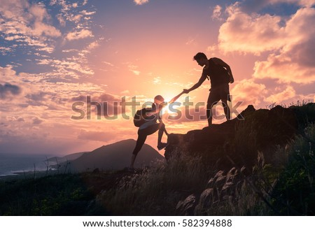 People helping each other hike up a mountain at sunrise.  Giving a helping hand, and active fit lifestyle concept. Royalty-Free Stock Photo #582394888