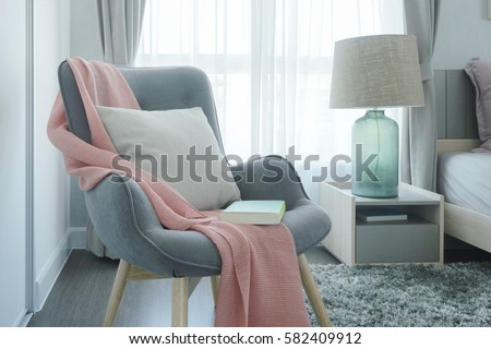 Gray easy armchair with pink scarf, pillow and book next to bed in the bedroom #582409912