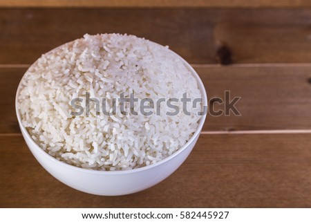 boiled rice in white bowl on the wooden background close up #582445927