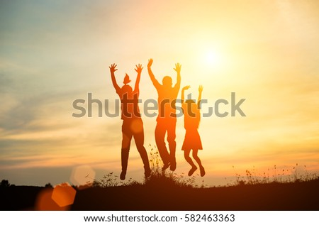 Silhouette group of friends having fun jumps on sunset and mountains backdrop  #582463363