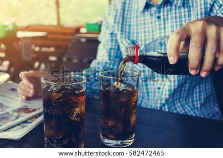 Women hand pour or fill drink in glass, double glass of soda on wooden table #582472465