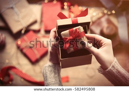 beautiful woman hands holding cute gift and putting it inside another one on the wonderful decoration background #582495808