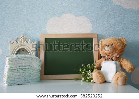 Diapers and blank chalkboard. Teddy bear dressed in diaper. frame with a copy space
