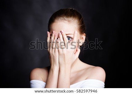 Young girl covered her face with fear Royalty-Free Stock Photo #582597946