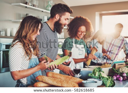 Good friends laughing and talking while preparing meals at table full of vegetables and pasta ready for cooking in kitchen Royalty-Free Stock Photo #582618685