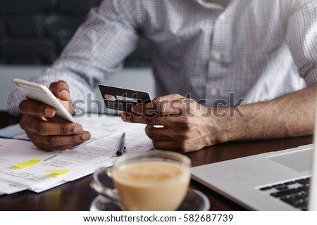 Close up shot of African man's hands holding mobile and credit card. Dark-skinned businessman checking account balance, using online banking application on his cell phone, drinking coffee at cafe Royalty-Free Stock Photo #582687739
