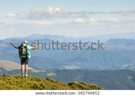 Hiker standing on top of mountain. Unity with nature concept. #582746812
