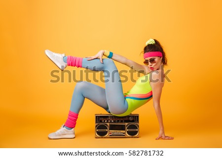 Attractive playful young woman athlete sitting on retro boombox and posing over yellow background #582781732