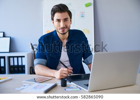 Portrait of freelance graphic designer sitting at desk with laptop and tablet #582865090
