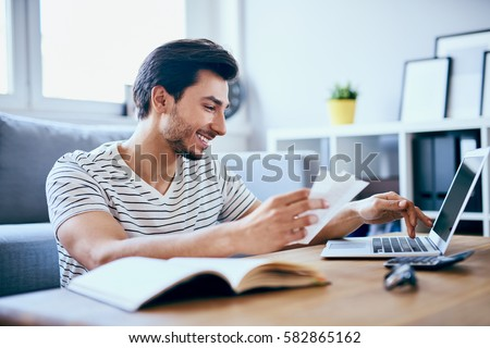 Happy man paying bills on his laptop in living room Royalty-Free Stock Photo #582865162