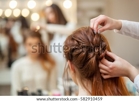 Beautiful, red-haired girl with long hair, hairdresser weaves a French braid, in a beauty salon. Professional hair care and creating hairstyles. Royalty-Free Stock Photo #582910459