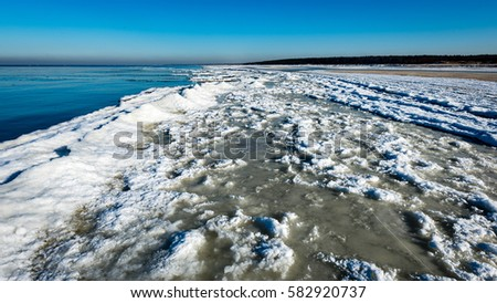 frozen beach in cold winters day with colorful sky and ice #582920737