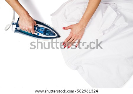 Female hand ironing clothes top view isolated on white background. Young woman with iron ironing man's shirt seen from above during housework. Blue iron on white table. #582961324