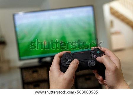 Man playing video game. Hands holding console controller. Football or soccer game on the television. Widescreen tv stands on commode. #583000585