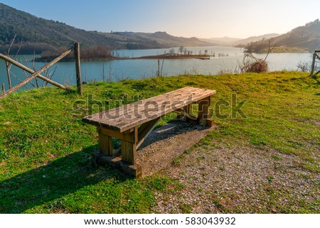 wooden bench against a beautiful lake on a sunny day with a clear blue sky #583043932