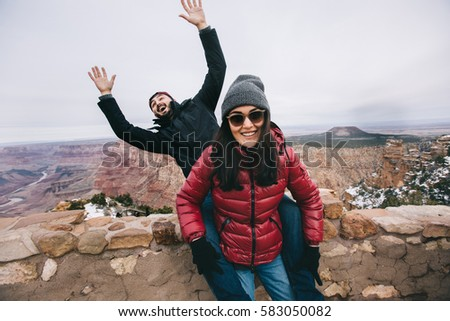 Happy couple having fun and taking funny picture for social media at Grand Canyon viewpoint, Arizona, USA.