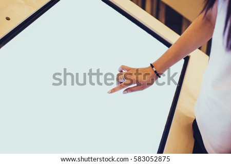A hand of a assistant typing on a blank large display of a professional tablet in bank or exhibition. Concept of business assistance, type your text. #583052875