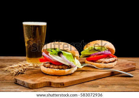 hamburger with mug of beer on wooden table. #583072936