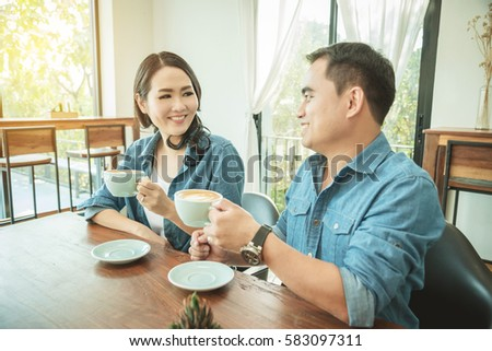 Asian couples look at each other and smile while drinking coffee together in a coffee shop #583097311