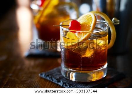 tasty alcoholic old fashioned cocktail with orange slice, cherry, and lemon peel garnish Royalty-Free Stock Photo #583137544
