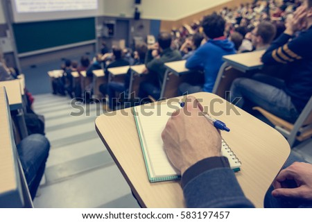 Taking notes at conference. Royalty-Free Stock Photo #583197457