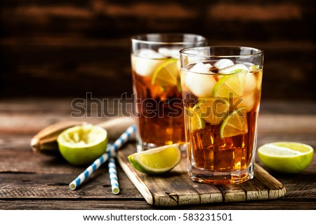 Cuba Libre or long island iced tea cocktail with strong drinks, cola, lime and ice in glass, cold longdrink or lemonade Royalty-Free Stock Photo #583231501