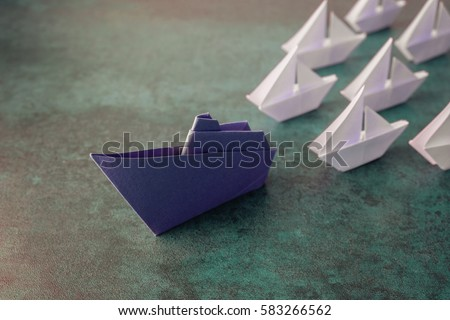 Origami paper ship with small sailboats, leadership, marketing concept, social media influencers, HR recruiter, disruptive innovation, standing out concept,New year 2020 business resolution  #583266562