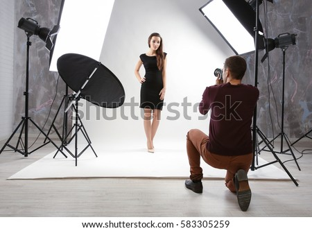 Photographer working with model in studio Royalty-Free Stock Photo #583305259