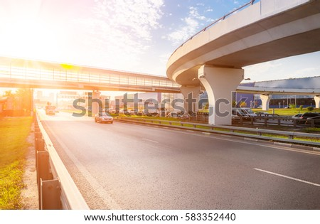 Highway interchange with bridge and sun on the background #583352440