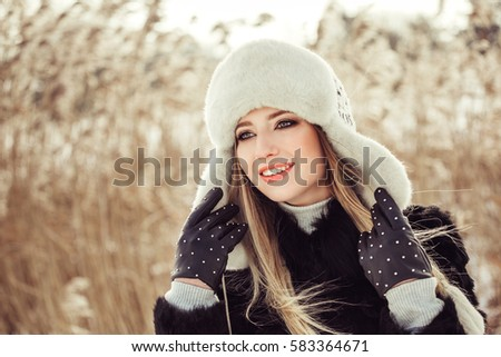 Winter close up portrait of young beautiful blonde in a winter hat and gloves smiling in white teeth and having a good time outdoors in the winter #583364671