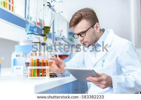 Young concentrated man scientist holding digital tablet and working with test tubes in lab #583382233